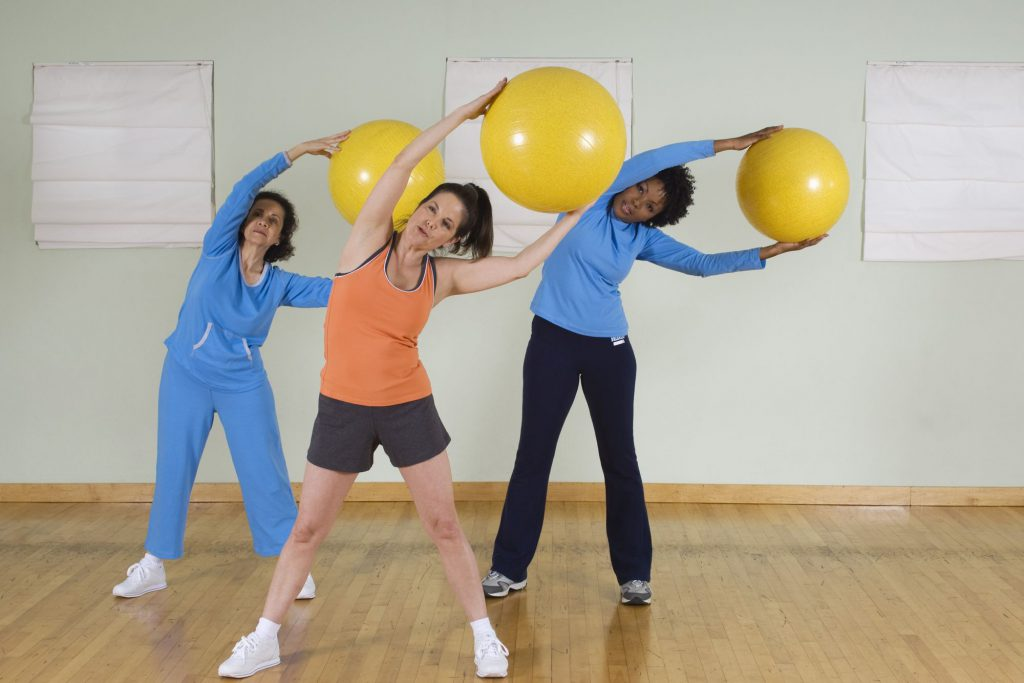 Women Using Exercise Balls in Fitness Class